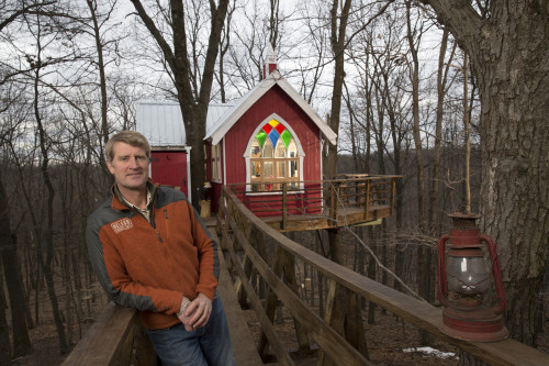 Pete Nelson, owner of Nelson Treehouse and Supply, poses by a Ohio brewery treehouse he designed on Animal Planet's