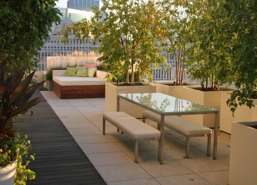 Ipe wood decking and concrete pavers give this rooftop patio by Chicago Specialty Gardens an contemporary, urban feel.