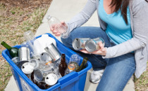 Woman putting cans and bottles in recycling bin