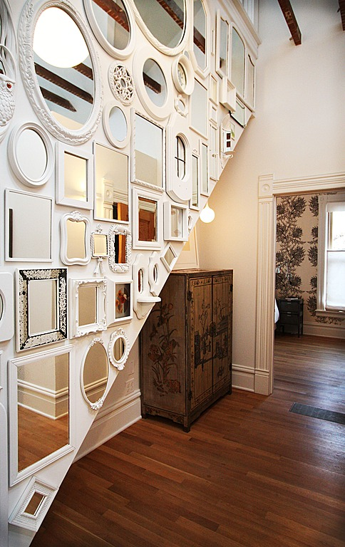 A varied gallery of mirrors is a great addition to this entry way design by bright designlab interior design.