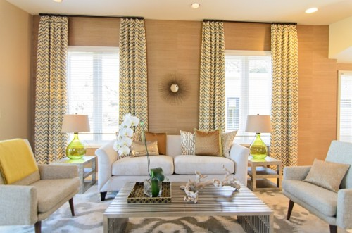 Source: American Dream Builders. A large print is on the rug, a medium print is on the drapes, and the pillows are a mix of solid colors and smaller prints that work with both.